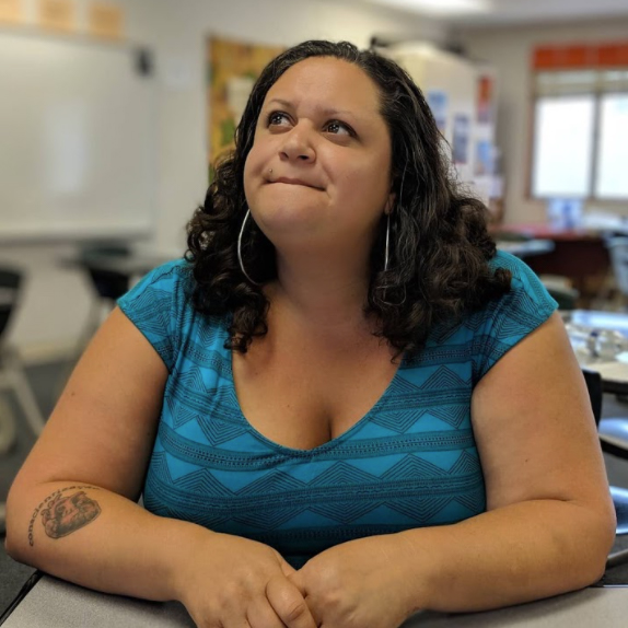 Photo of Chela Delgado, a mixed Black teacher in her classroom, looking off to the side in thought.