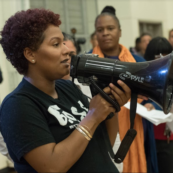 "Desiree McSwain-Mims, 2018 on a megaphone at an OUSD community board meeting speaking on behalf of the immediate need to eliminate the Oakland Schools Police Department. She is wearing a Black shirt that says ""B.O.S.S Bettering Our School System"""