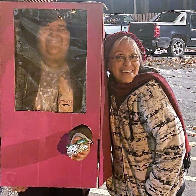 Full-length photo of Charlene with a smiling Penobscot youth. Charlene is smiling, wearing a maroon hat and matching scarf, a black and white hoodie and a long black skirt. Her silver hair is visible under her hat and she has glasses. Beside her is a non-binary child in a Halloween costume that looks like a pink Barbie Doll box.