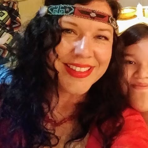Photo of Dawn from the shoulders up. Dawn is smiling,.  wearing a red top, red lipstick, and a beaded headband beaded in black, red, white, and teal design that crosses Dawn's forehead over long,  black, and curly hair.  In the cream background, the partial face of a young person smiles from behind Dawn's shoulder.