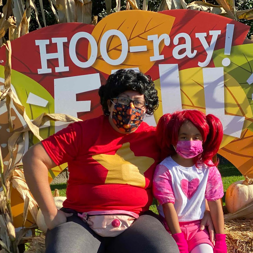 Photo of Mariposa sitting on a block of hay in front of a sign with the letters HOO-ray! next to a child dressed as Spinel, a crystal gem.  Mariposa does cos-play being Steven Universe wears a dark haired curly wig, a covid- facemask, and a red shirt with a gold star on it, with a rose quartz belly.
