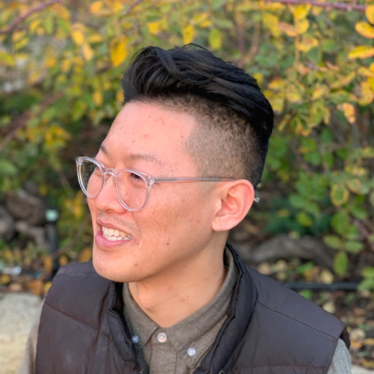 Andrew, a light-skinned East Asian person with dark brown hair, cut short on the sides, smiles in three-quarter profile. He is wearing glasses, a brown vest, gray button-up, with green and yellow leaves in the background.