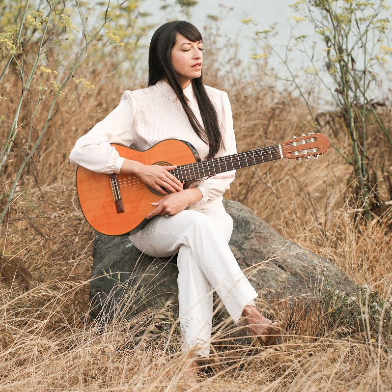 Photo of Diana sitting down on a tall rock, resting her acoustic guitar on her lap. She's surrounded by dry grass and tall fennel plants, behind her there's a view of water, at  Berkeley Bay. Diana is a mexican light-skinned woman with long black hair. She looks to the horizon, she's wearing white pants and light pink blouse.